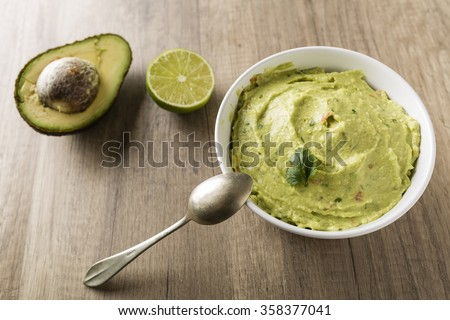 Guacamole with avocado, lime, tomato, and cilantro on wooden table - stock photo