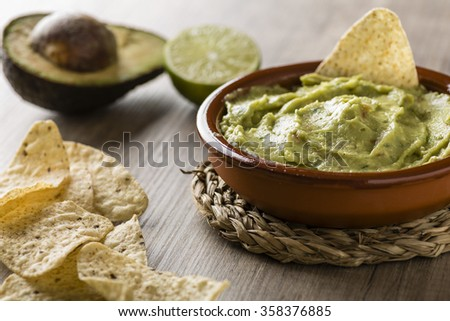 Guacamole with avocado, lime, tomato, and cilantro with tortilla chips on wooden table