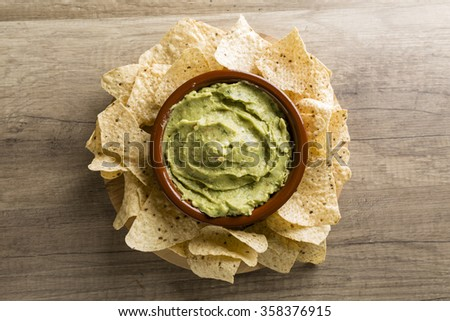 Guacamole with avocado, lime, tomato, and cilantro with tortilla chips on wooden table - stock photo