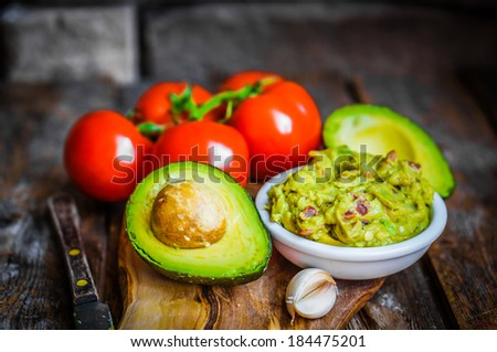 Guacamole with bread and avocado on rustic wooden background - stock photo