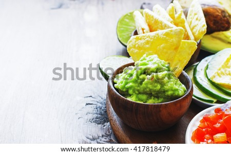 Guacamole with fresh ingredients on a table with tortilla chips on dark wooden board. ,selective focus. - stock photo