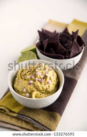 Guacamole with Red Onion and Blue Corn Chips - stock photo
