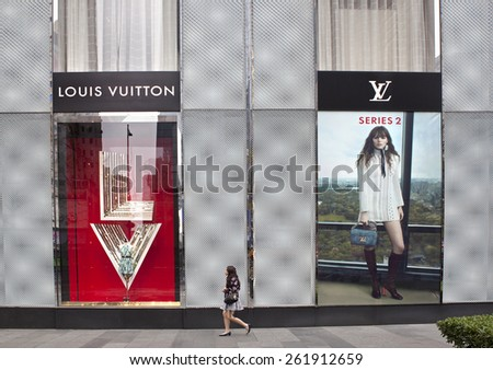 GUANGZHOU, CHINA - FEBRUARY 24, 2015: A woman walks nearby a Louis Vuitton store; Louis Vuitton, a French fashion house founded in 1854, operates more than 460 stores worldwide.  - stock photo
