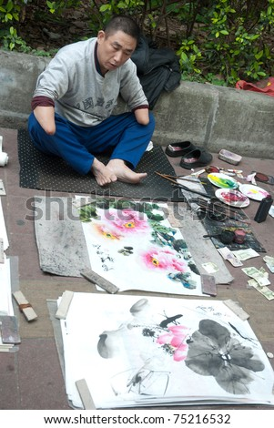 GUANGZHOU, CHINA - MARCH 26: Unidentified hand disabled painter use his foot drawing Chinese ink wash pictures on March 26, 2011 in Guangzhou, China.