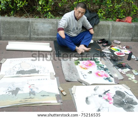 GUANGZHOU, CHINA - MARCH 26: Unidentified hand disabled painter use his foot drawing Chinese ink wash pictures on March 26, 2011 in Guangzhou, China. - stock photo