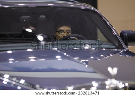 GUANGZHOU, CHINA - NOV. 20. 2014: Man seating in Rolls Royce car on the 12th China International Automobile Exhibition in Guangzhou, Guangdong province. - stock photo