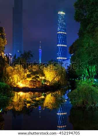 GUANGZHOU, CHINA - NOVEMBER 7, 2015: Amazing night view of the Zhujiang New Town (the Pearl River New Town) from park. The Canton Tower and the Guangzhou International Finance Centre reflected in pond - stock photo