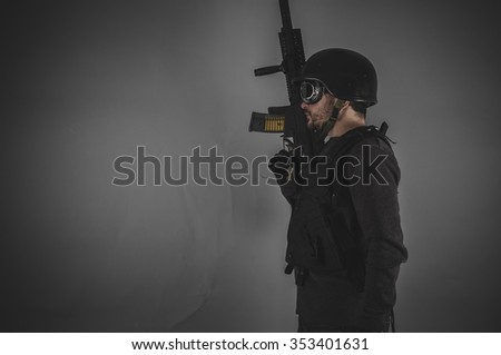 guard, airsoft player with gun, helmet and bulletproof vest on gray background