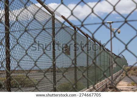 Guarded border - barbwire and fence - stock photo