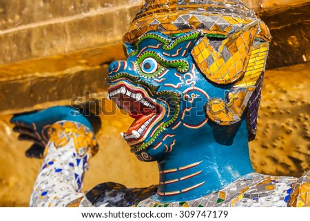 Guardian demon holding Golden Chedi of Wat Phra Kaew Temple in Bangkok, Thailand