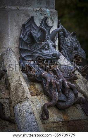 guardian, devil figure, bronze sculpture with demonic gargoyles and monsters - stock photo