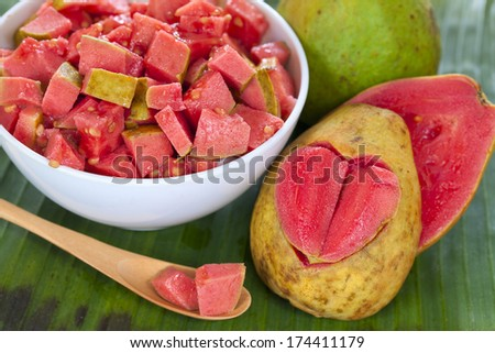 Guava fruit salad and halves pink guava with carved heart on green leaf background