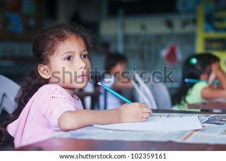 GUAYAQUIL, ECUADOR - FEBRUARY 8: Unknown kid in lesson drawing in primary school by project to help deprived children in deprived areas with education, February 8, 2011 in Guayaquil, Ecuador. - stock photo