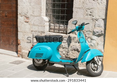 GUBBIO, ITALY -MAY 13; Bright aqua Vespa motor scooter parked in Italian village street under barred window in stone wall.May 13, 2011 in Gubbio, Italy. - stock photo
