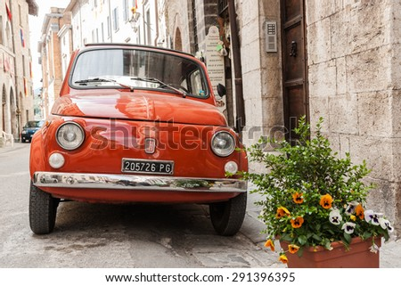 GUBBIO, ITALY - MAY 13; Iconic Italian orange Fiat car parked in traditional stone narrow street  high walls of homes and buildings dwarfing it on both sides on May 13, 2011, Gubbio,  Umbria, Italy,