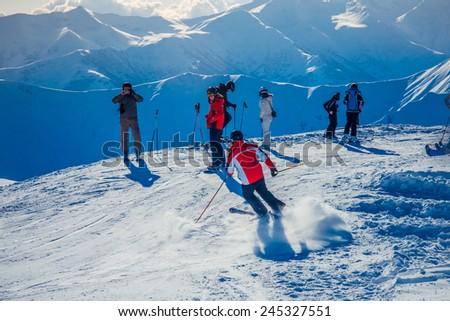 GUDAURI, GEORGIA - DECEMBER 25, 2014 - Group of snowboarders and skiers in winter resort Gudauri, Georgia, Caucasus mountains. - stock photo