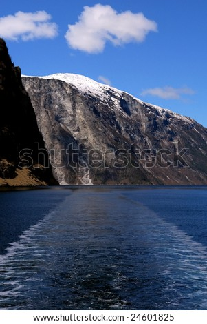 Gudvangen fjord landscape, mountain in the background and boat trail,  Norway