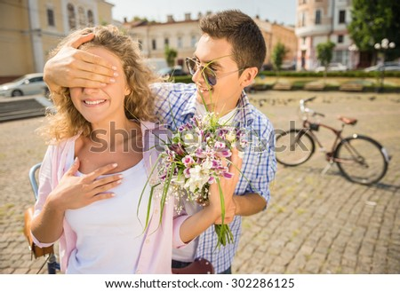 Guess who? Young man closed eyes his girlfriend making surprise with flowers while both standing at the city street. - stock photo