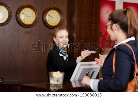 Guest at an international hotel requesting a business card at reception from the beautiful stylish receptionist - stock photo