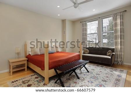 Guest bedroom in luxury home with orange bedspread - stock photo
