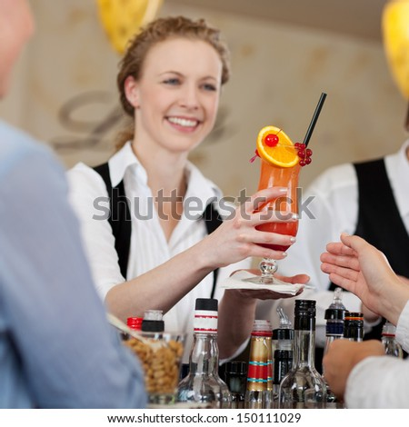 Guest being served a colourful orange and rum tropical cocktail by a smiling barmaid in a hotel or restaurant - stock photo