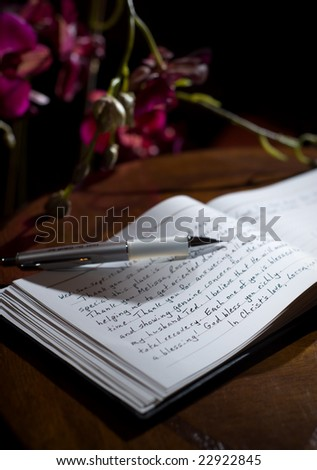 Guest-book with 'thank you' notes and orchids - stock photo