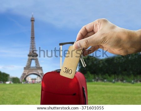 guest holding the hotel room key at Paris with Eiffel Tower in the background - stock photo