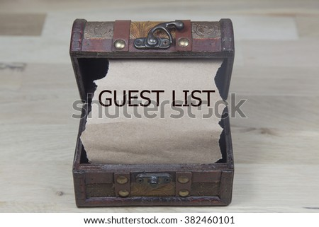 guest list is written on the Brown torn paper in the treasure box. wooden background