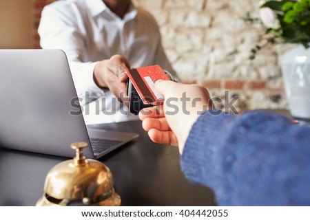 Guest makes card payment at check-in desk of hotel, detail - stock photo