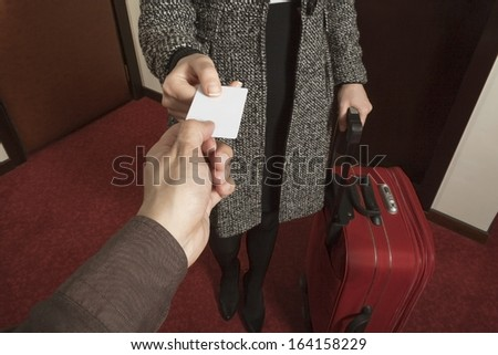 Guest receives room key from the hotel bellhop - stock photo
