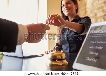 Guest takes room key card at check-in desk of hotel, close up - stock photo