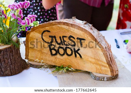 Guestbook sign is made from a crosscut section of a fir tree with the letters guest book burned into the wood grain at a wedding ceremony. - stock photo