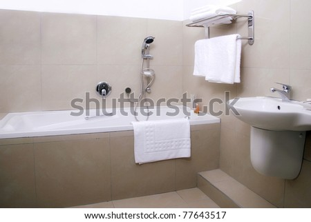 Guesthouse bathroom showing a bath with fresh towels - stock photo
