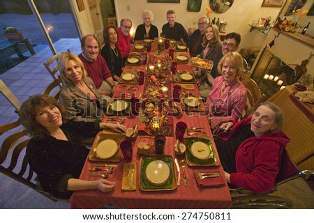 Guests at an elegant Thanksgiving dinner party - stock photo