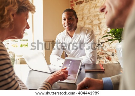 Guests checking in at a hotel using a tablet computer - stock photo