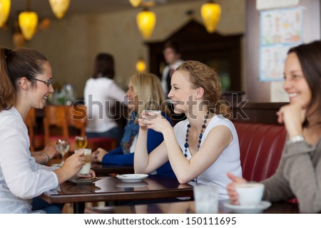 Guests enjoying coffee in a restaurant with focus to two stylish young woman sitting at a table together - stock photo