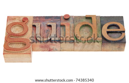 guide word in vintage wood letterpress printing blocks, stained by color inks, isolated on white