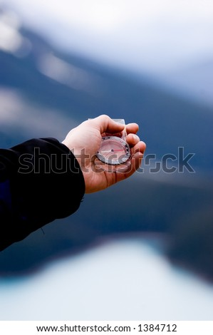 Guiding with compass in the mountains - stock photo