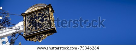 Guildford Clock banner Guildford High Street clock on a deep blue sky placed far left to give room for text - stock photo