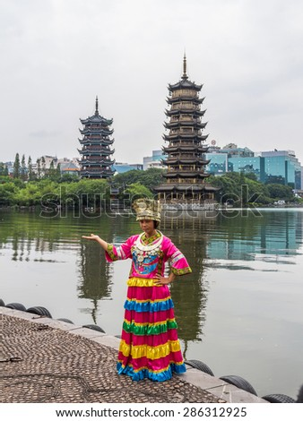 GUILIN, CHINA - MAY 02, 2015: An unidentified Chinese tourist dressed up in traditional cloths poses in front of Sun and Moon Pagodas in Guilin, China. Guilin is a famous tourist destination in China. - stock photo