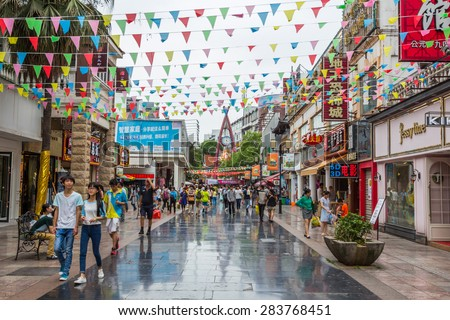 GUILIN, CHINA - MAY 02, 2015: Unidentified people walking through the main shopping street in Guilin, China. Guilin is a city in southern China known for its dramatic landscape of limestone karst. - stock photo