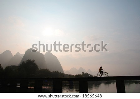 GUILIN, CHINA - SEPTEMBER 2008. A cyclist crosses a bridge in Guilin - stock photo