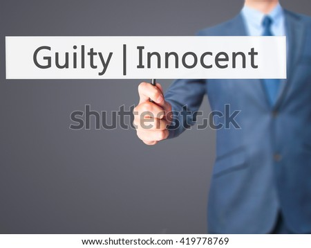 Guilty Innocent - Businessman hand holding sign. Business, technology, internet concept. Stock Photo - stock photo