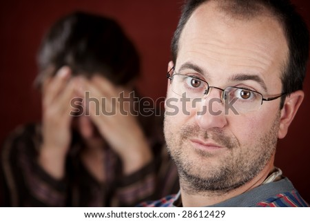 Guilty man with upset woman in the background - stock photo
