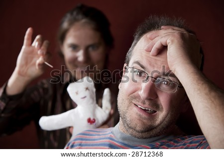 Guilty man with upset woman poking voodoo doll in the background - stock photo