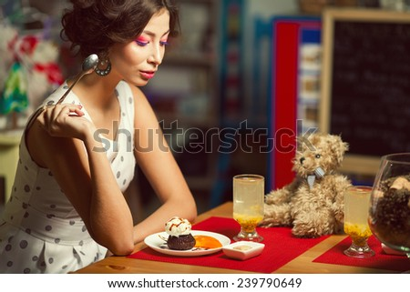 Guilty pleasure concept. Portrait of doll like brunette girl with retro hairdo in white trendy vintage polka-dot sleeveless dress eating cake, drinking tea in cafe. Close up. Copy-space. Indoor shot - stock photo