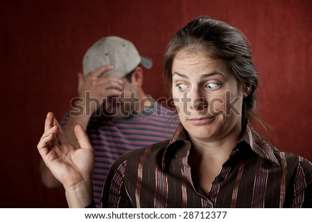 Guilty woman with upset man in the background - stock photo