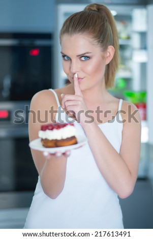 Guilty young woman preparing to eat a cake making a hushing gesture with her finger to her lips as she asks for secrecy - stock photo