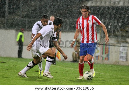 GUIMARAES, PORTUGAL - AUGUST 25: Filipe Luis(R),At.Madrid(ESP),protects the ball from Alex and Targino,Vitoria SC(POR),at the 2011\2012 UEFA Europa League on August 25, 2011 in Guimaraes, Portugal - stock photo