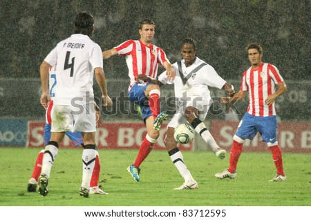GUIMARAES, PORTUGAL - AUGUST 25: Gabi Arenas(L)of At.Madrid(ESP) and Edgar Silva of Vitoria SC(POR), play under heavy rain at the 2011\12 UEFA Europa League match on August 25, 2011 in Guimaraes, Portugal - stock photo